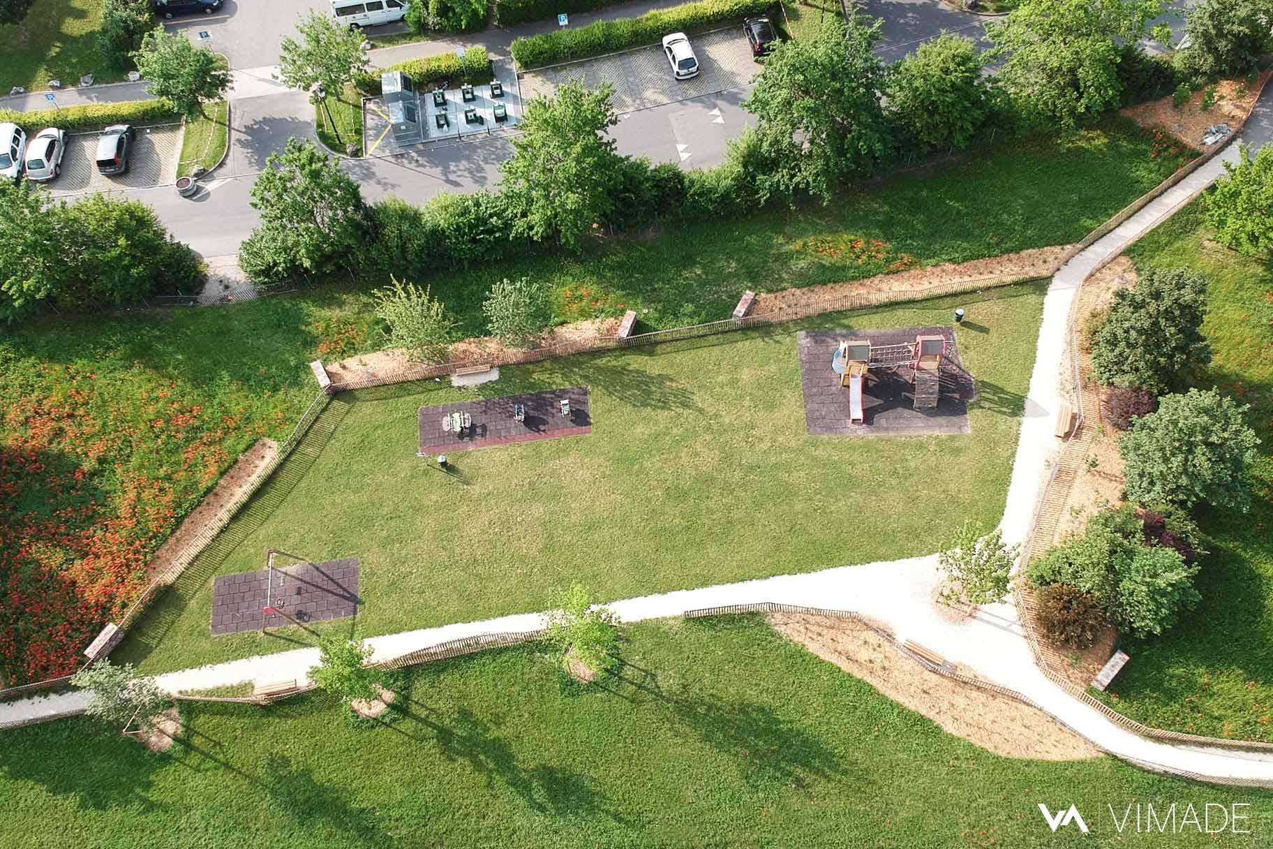Vue aérienne drone du projet écologique au parc des Tuileries à Bellevue offrant prairies, hôtels à insectes, végétation indigène et espaces d'agrément, VIMADE Architectes paysagistes Genève.