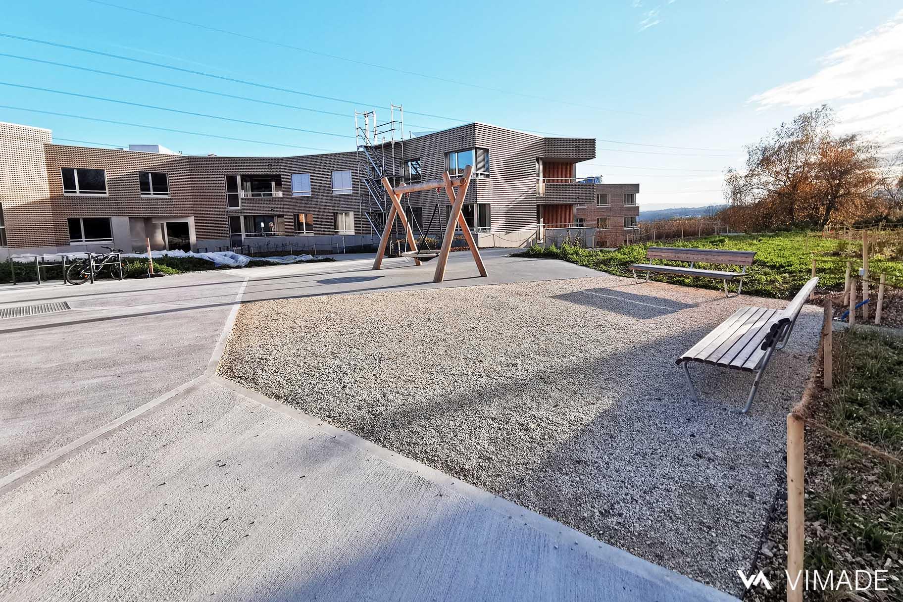 Place en stabilisé calcaire avec bancs et éléments de jeux en bois avec béton balayé, VIMADE Architectes paysagistes